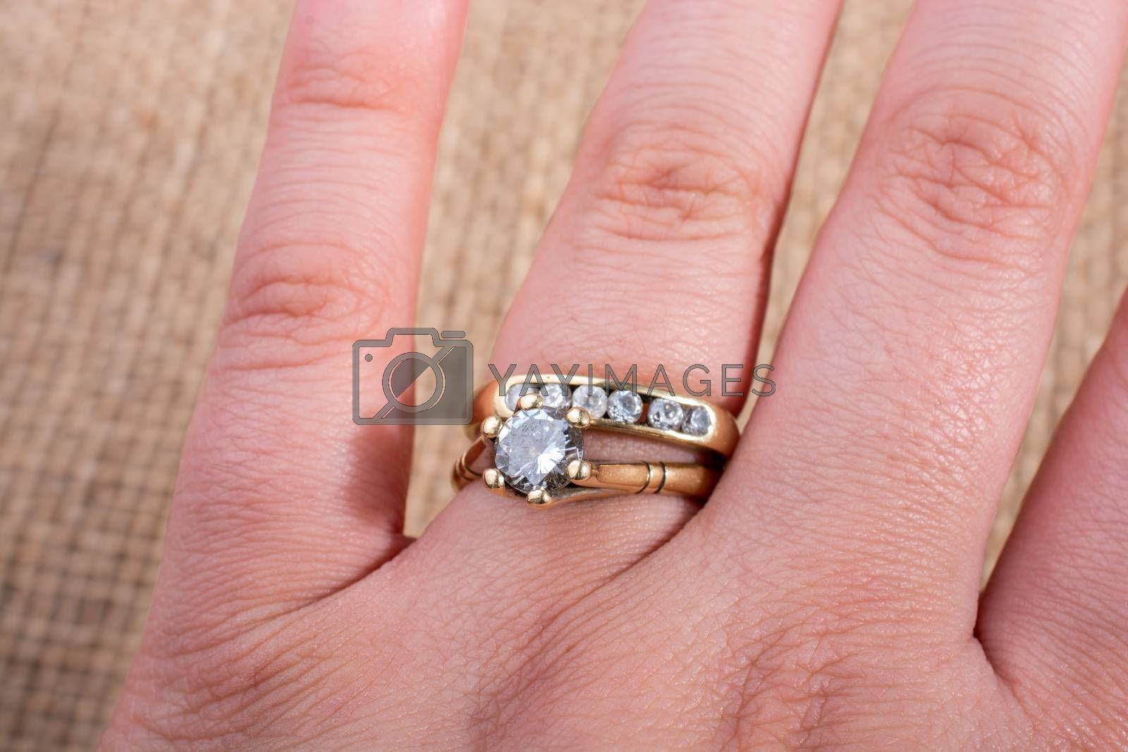 Hand wearing a fake  diamond ring on a textured background