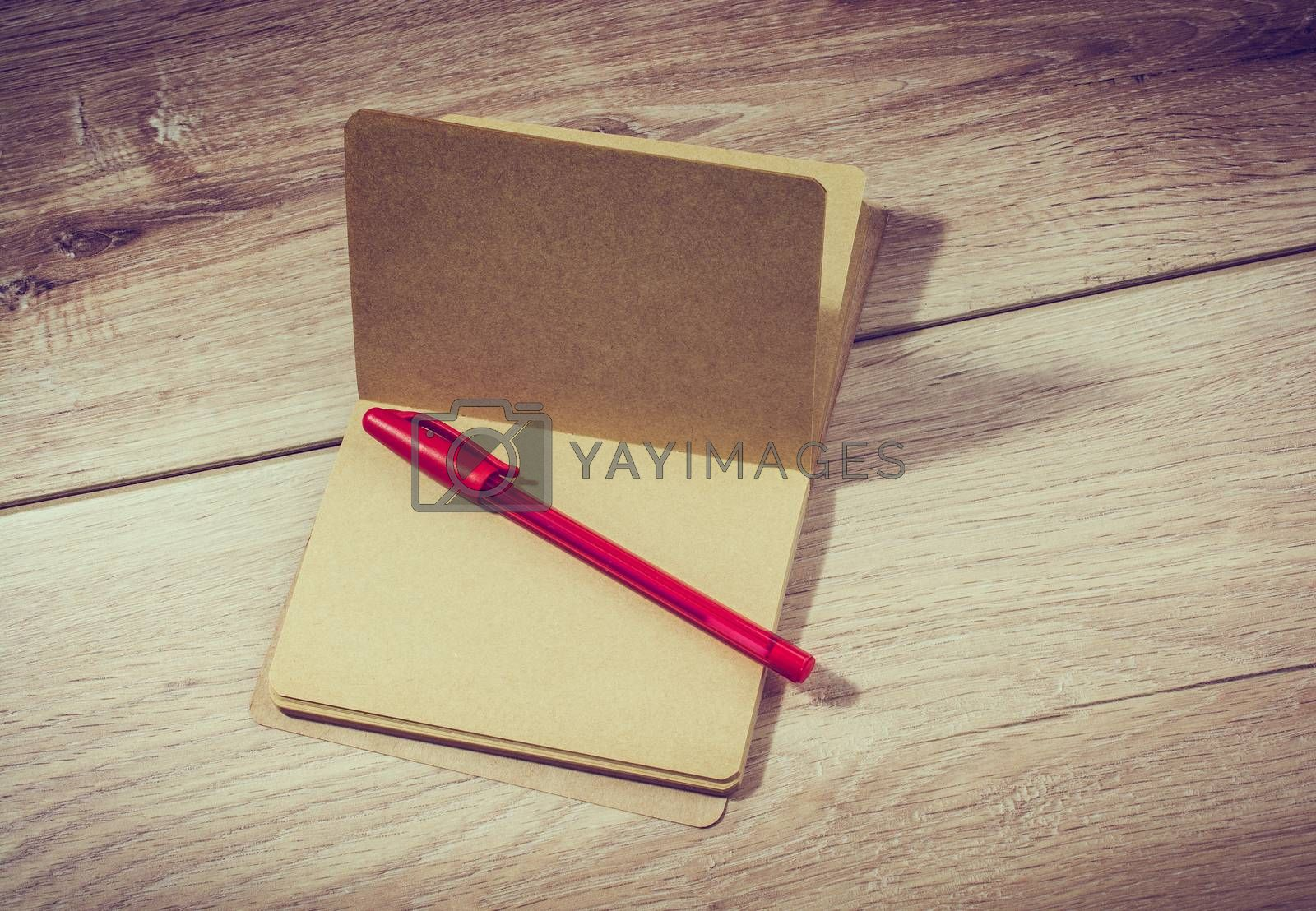 Brown color open notebook and a pen on wooden texture