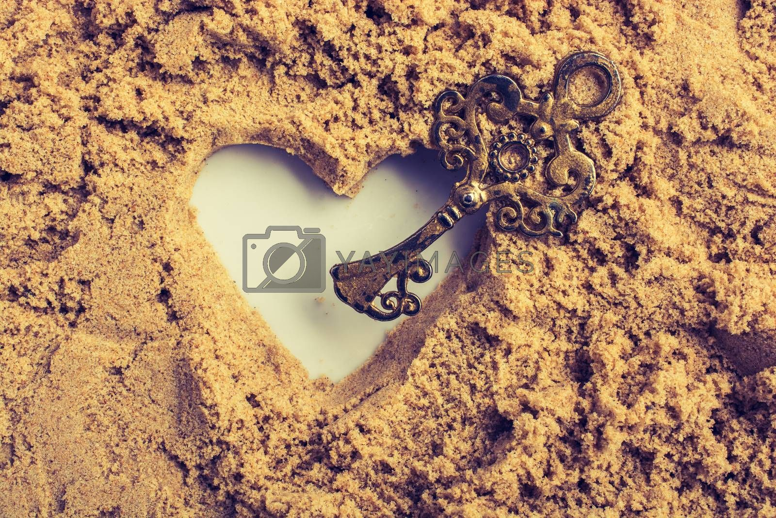 Retro style key and a heart shape made on brown sand
