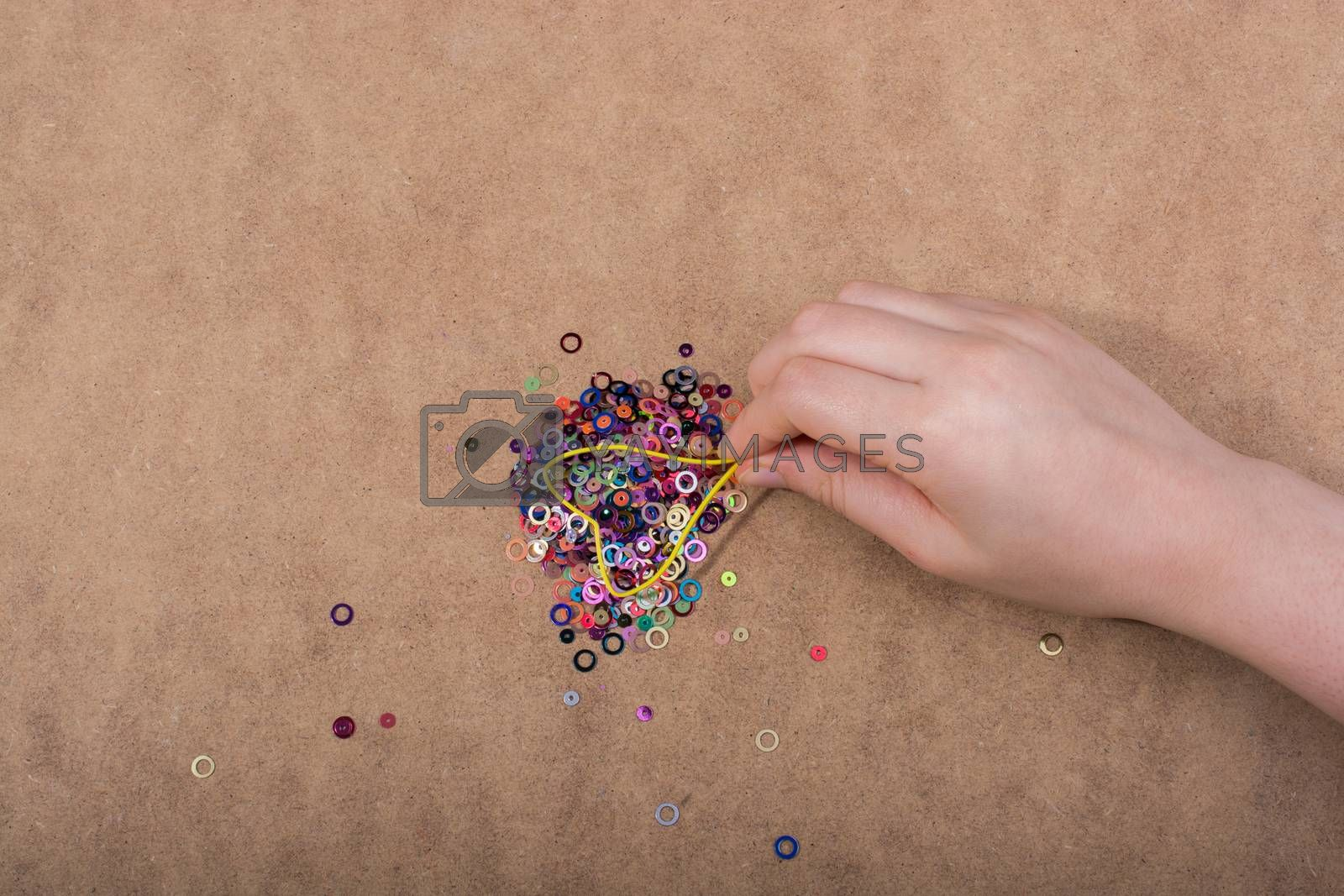 Hand holding decorative shiny colorful confetti on a wooden background