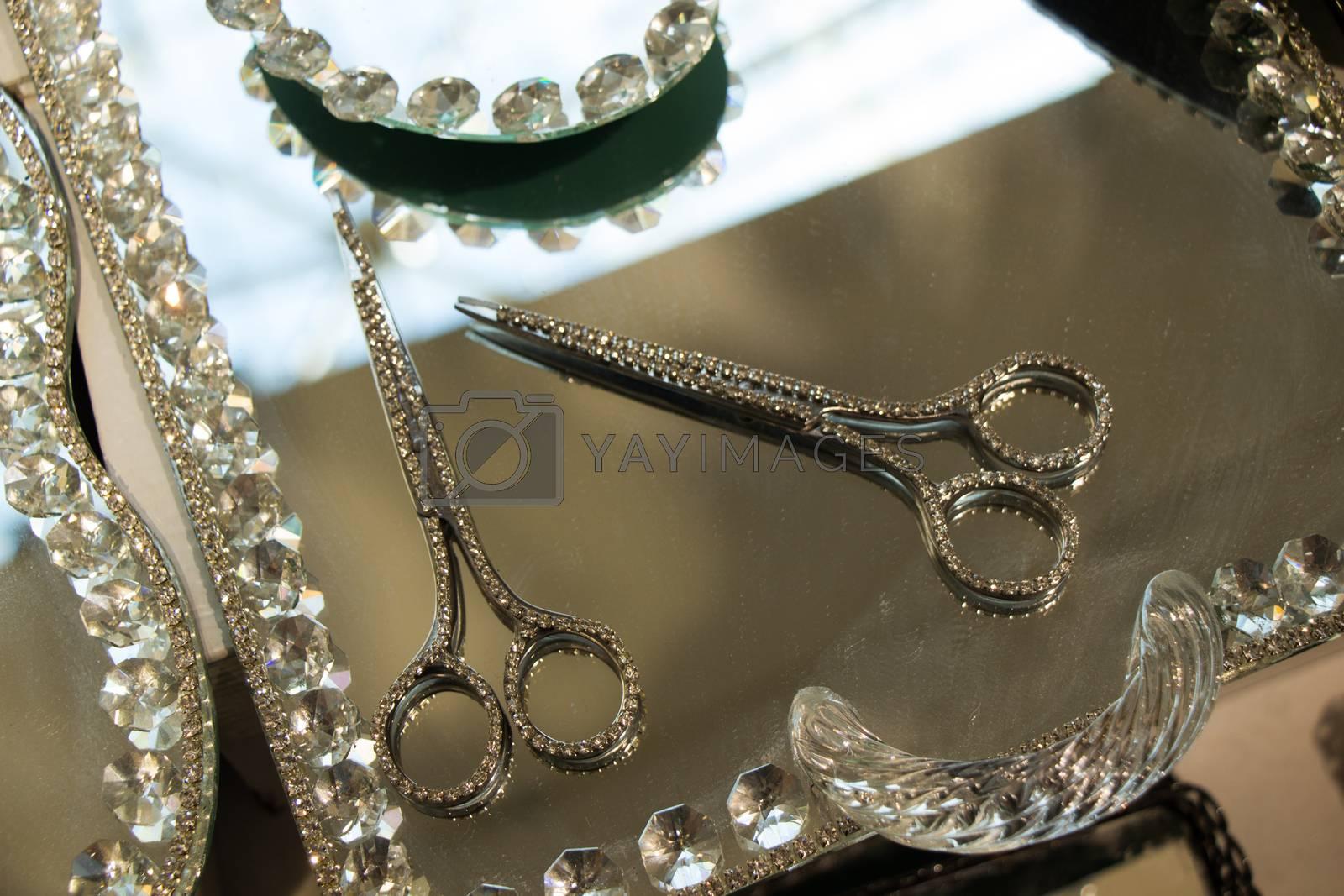 Metal scissors with diamonds on it on a mirror