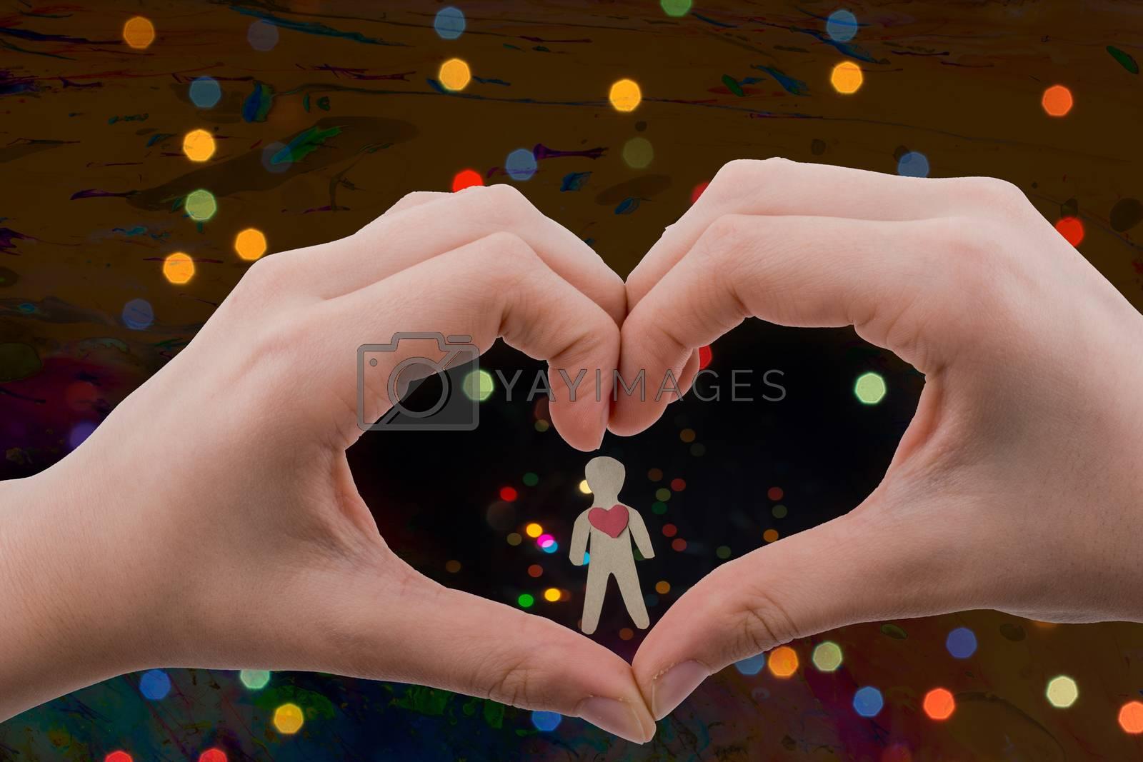 Paper man seen behind a heart shaped hand