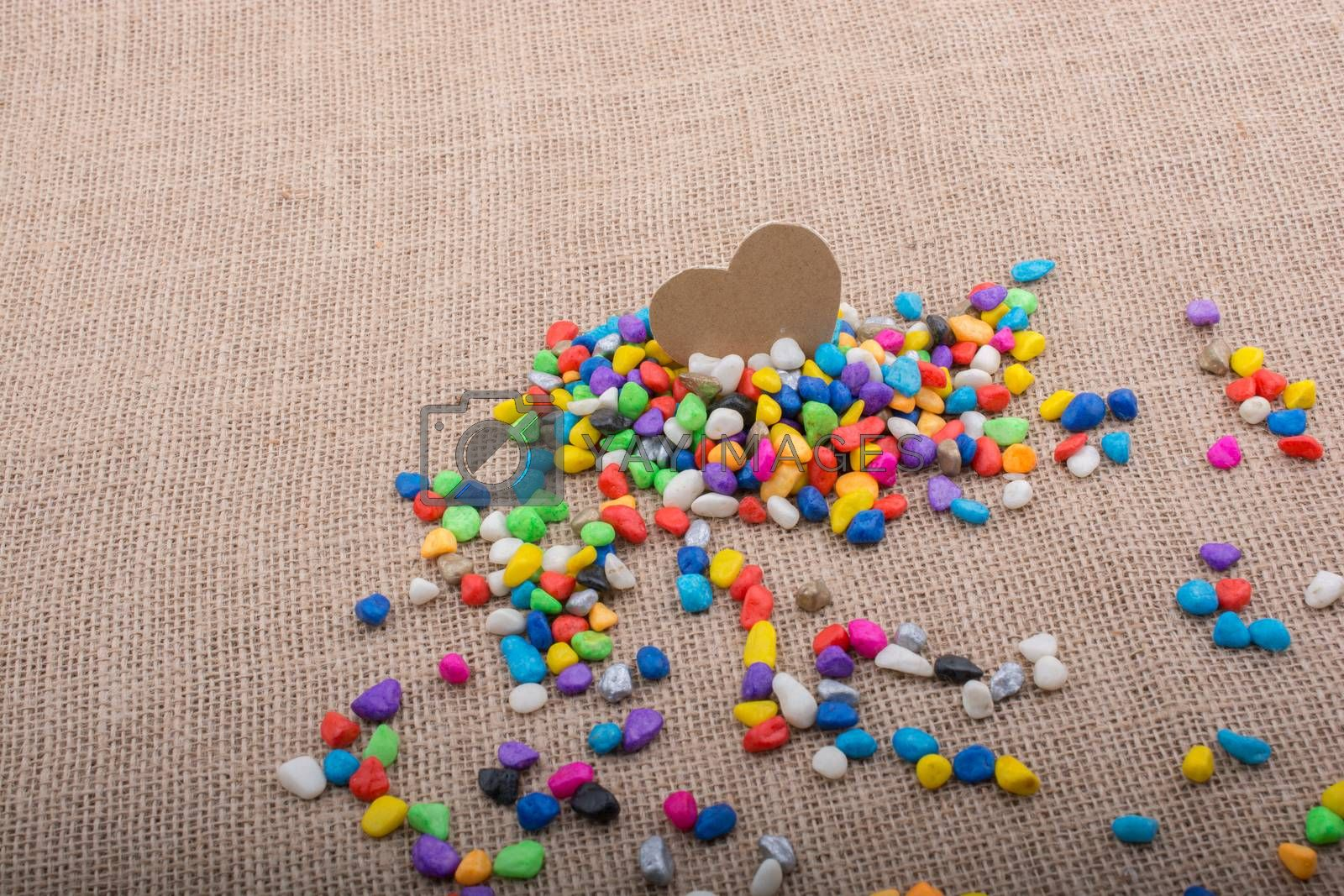 Paper heart amid colorful pebbles on canvas ground