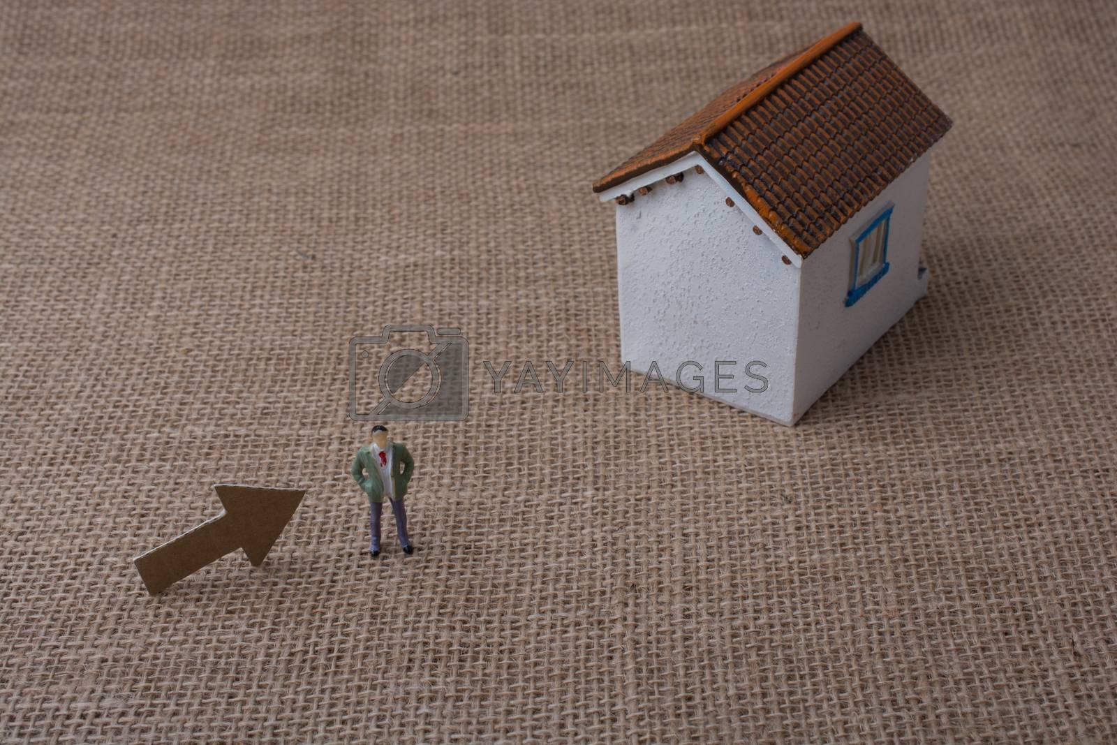 Model house and an arrow beside a man figure on a canvas