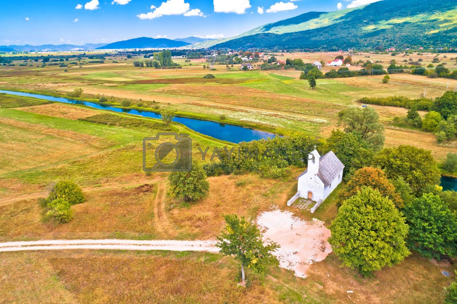 Stone church by Gacka river aerial view, Lika region of Croatia