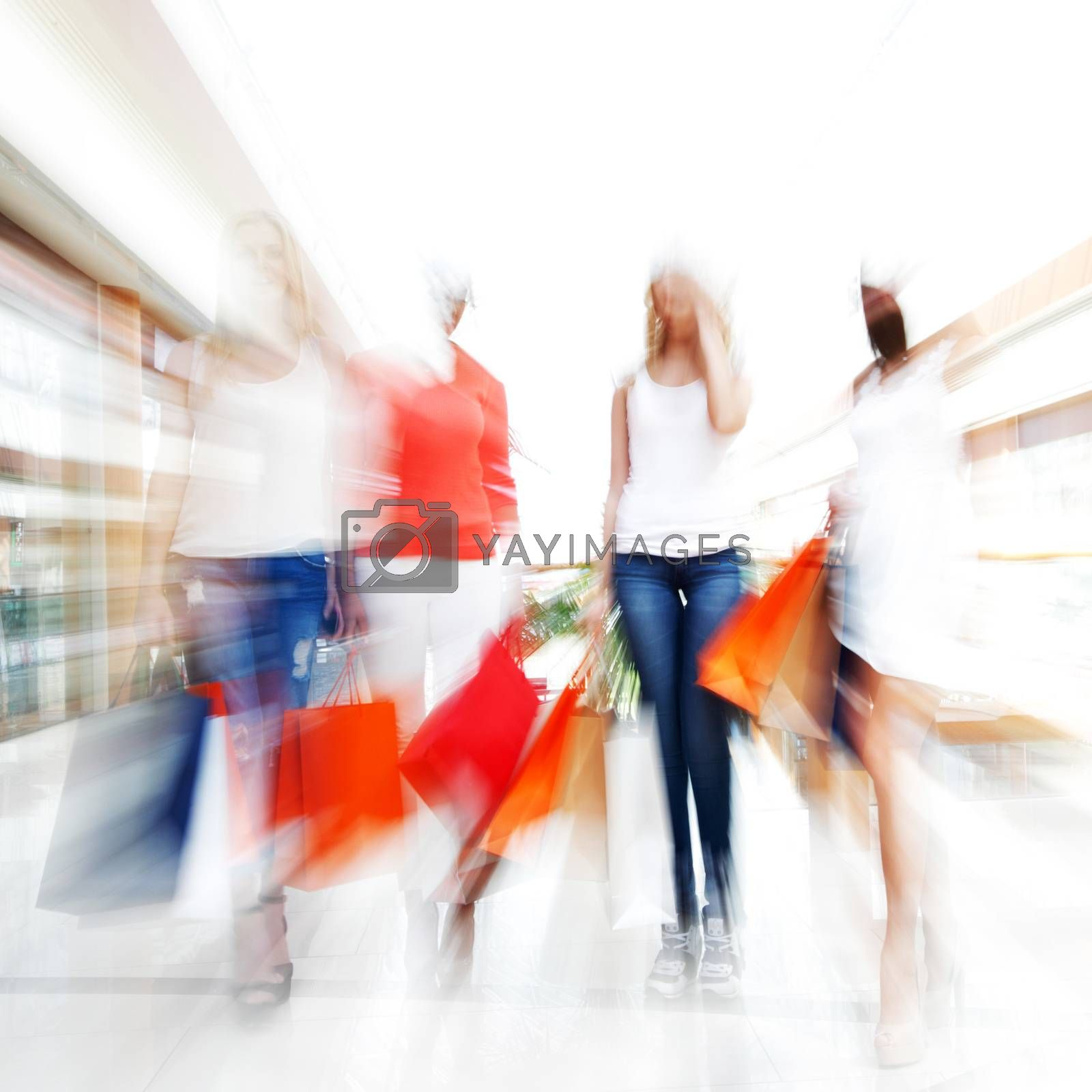 Women walking fast in shopping mall with bags , conceptual abstract background