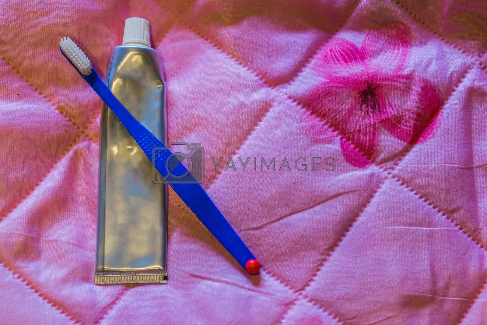 simple tooth brush with a silver blank tube of tooth paste, isolated on a pink background