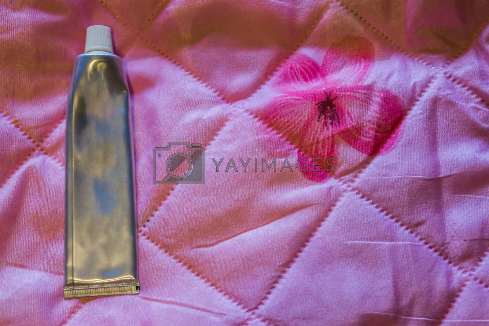 cosmetic products a blank silver tube isolated on a pink background