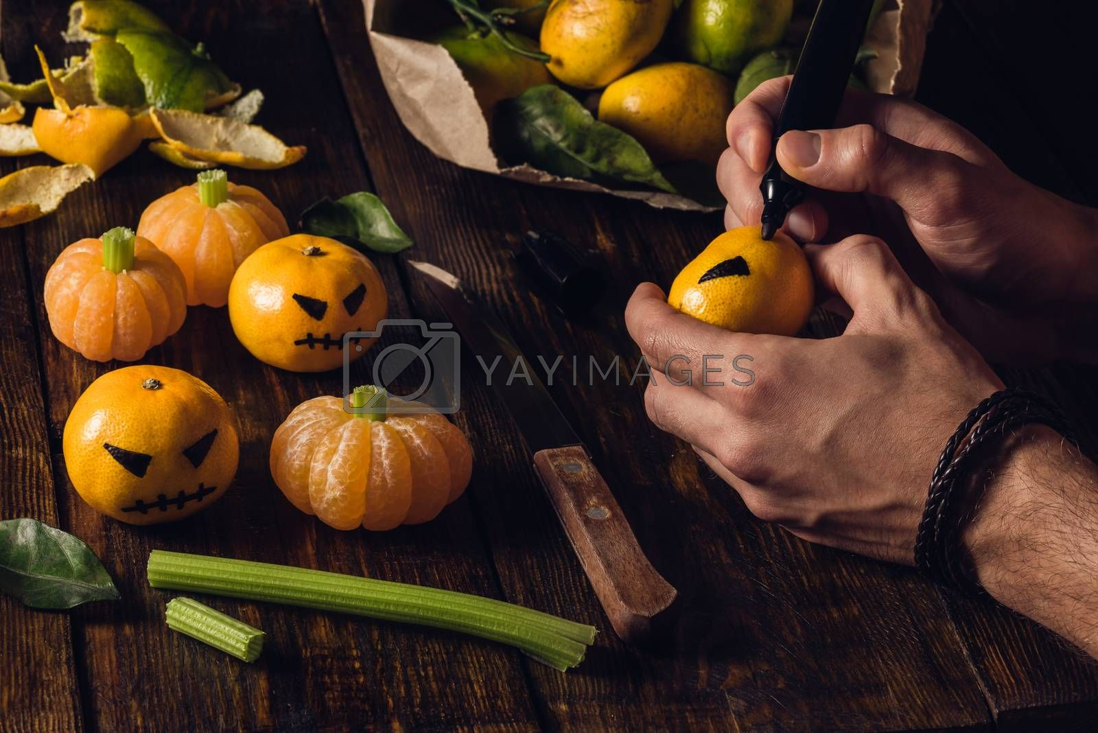 Preparation for Halloween. Young man draws a scary face on tangerines