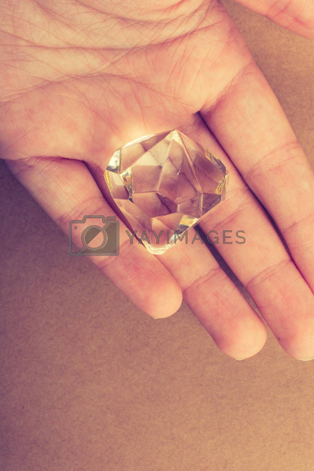 Fake diamond stone in hand in view