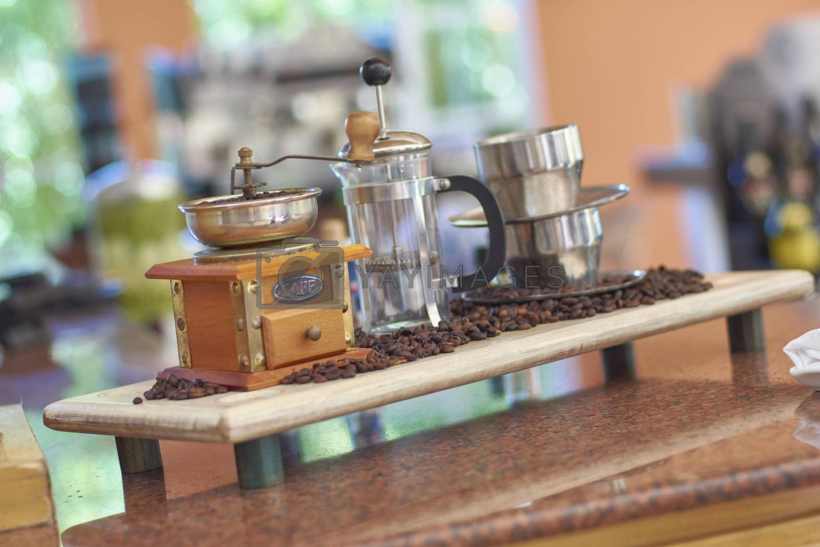 Still life with a vintage coffee grinder, coffee beans and other objects for the preparation of a good coffee.