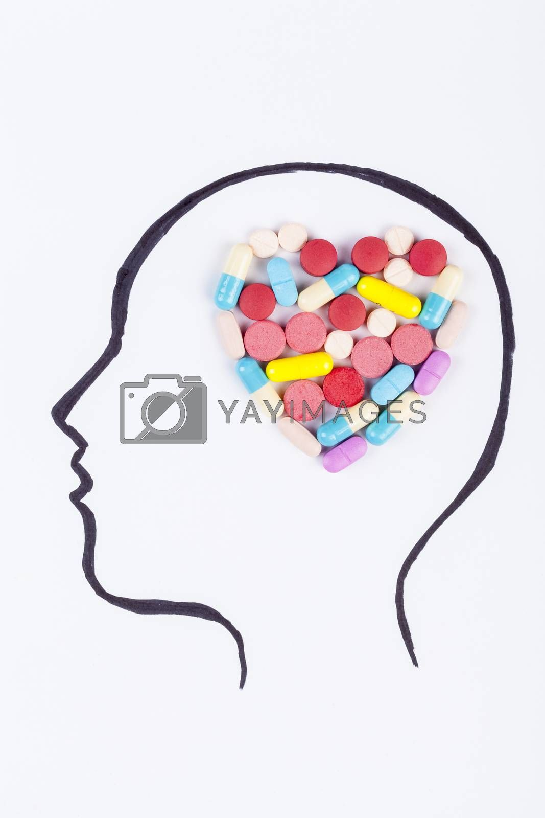 Human head hand drawing with heart shape colored pills in the brain