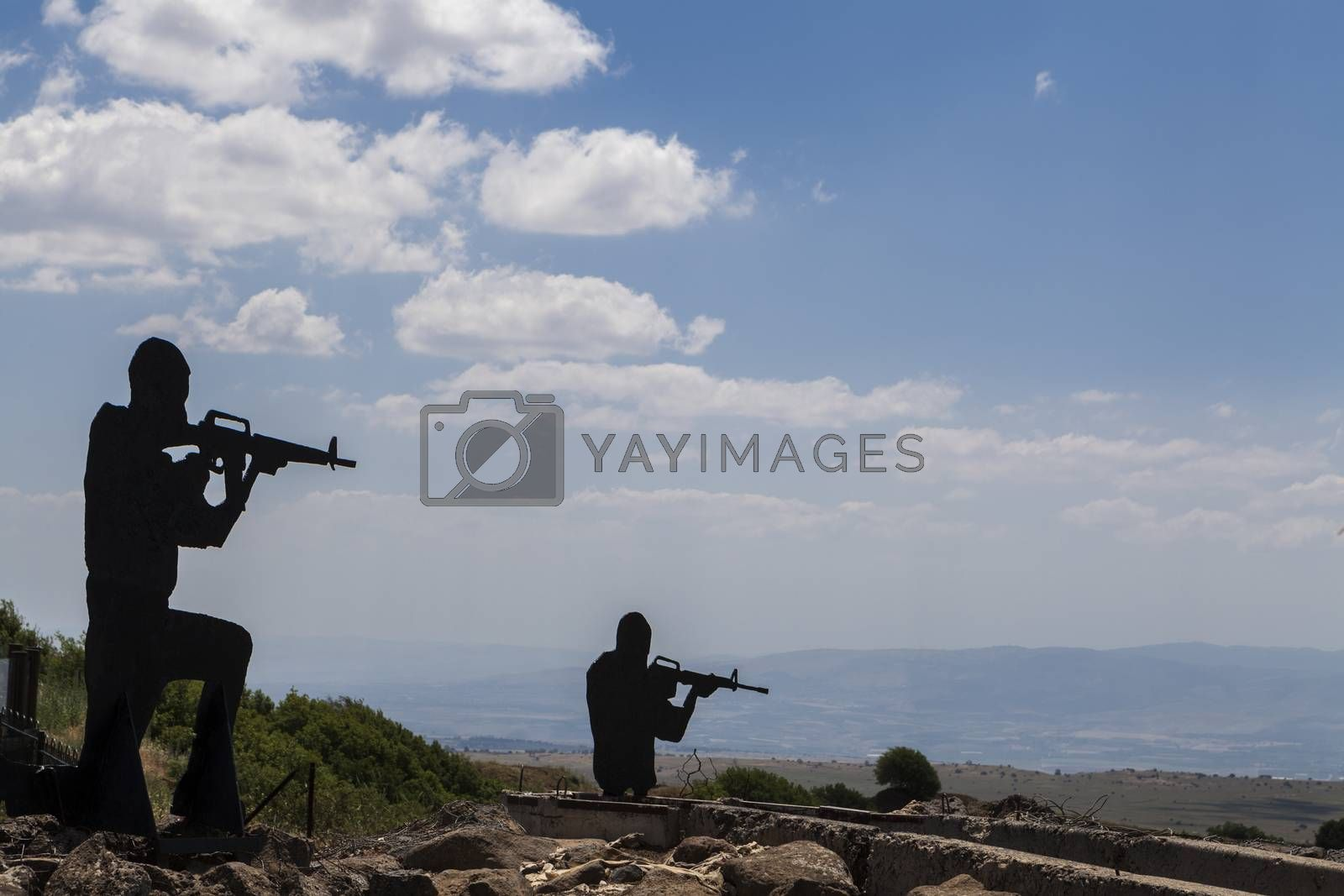 Two Soldiers silhouetts with blue sky in the background and rock reinforments in the foreground
