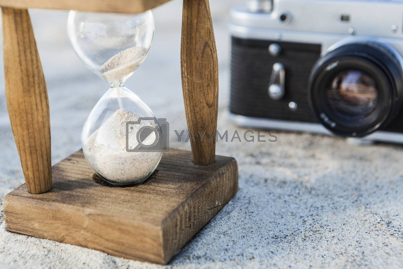 Vintage hourglass and camera in the sand at the beach