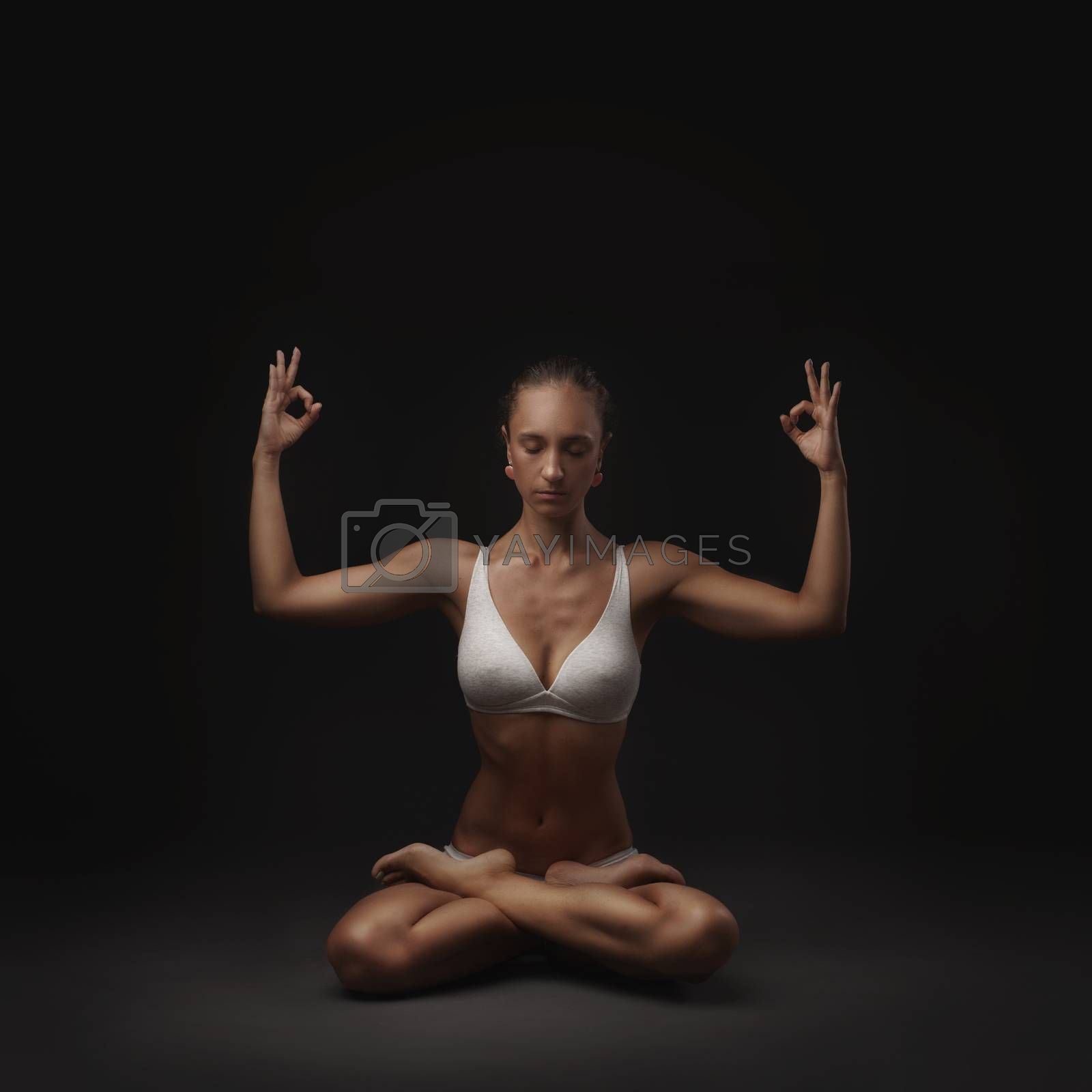 studio shoot of healthy latino woman doing yoga isolated on dark background