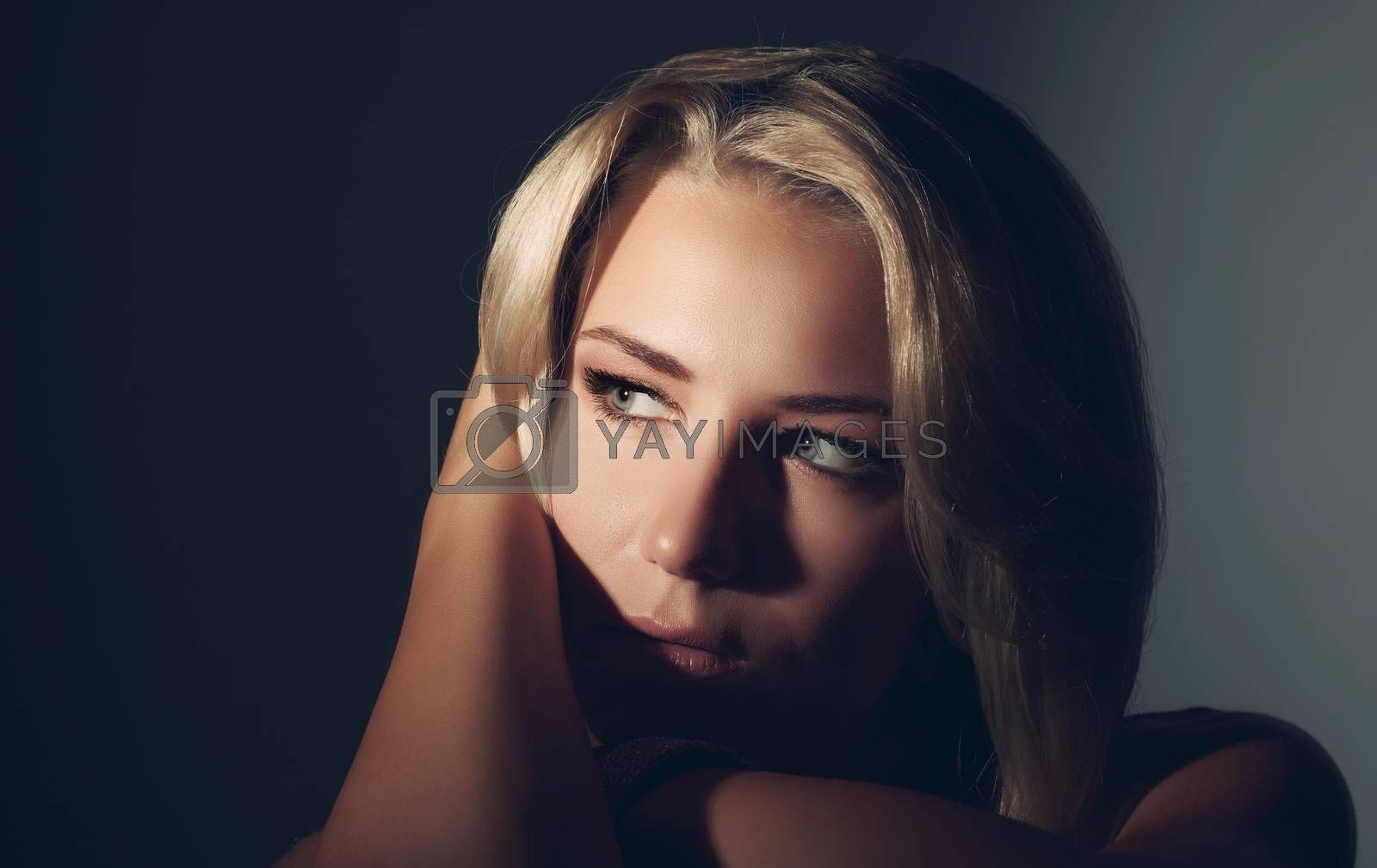 Closeup fashion portrait of a beautiful blond woman over dark background, sensual female with seductive look