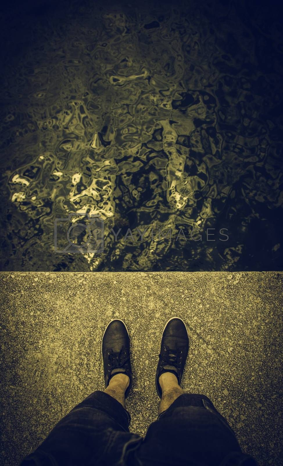 Feet on the water's edge, detail of exploration and contemplation