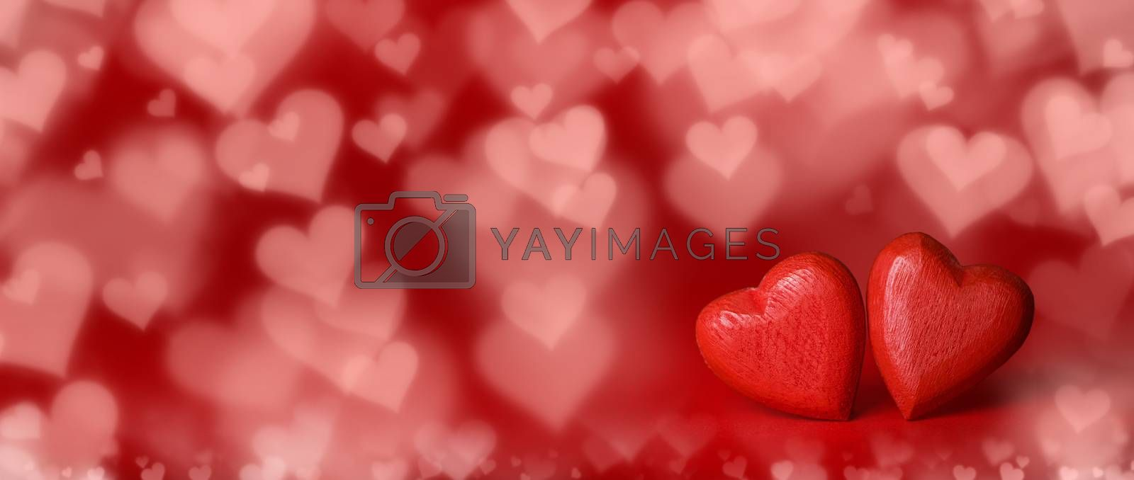 Two red glitter hearts on bright heart lights bokeh background