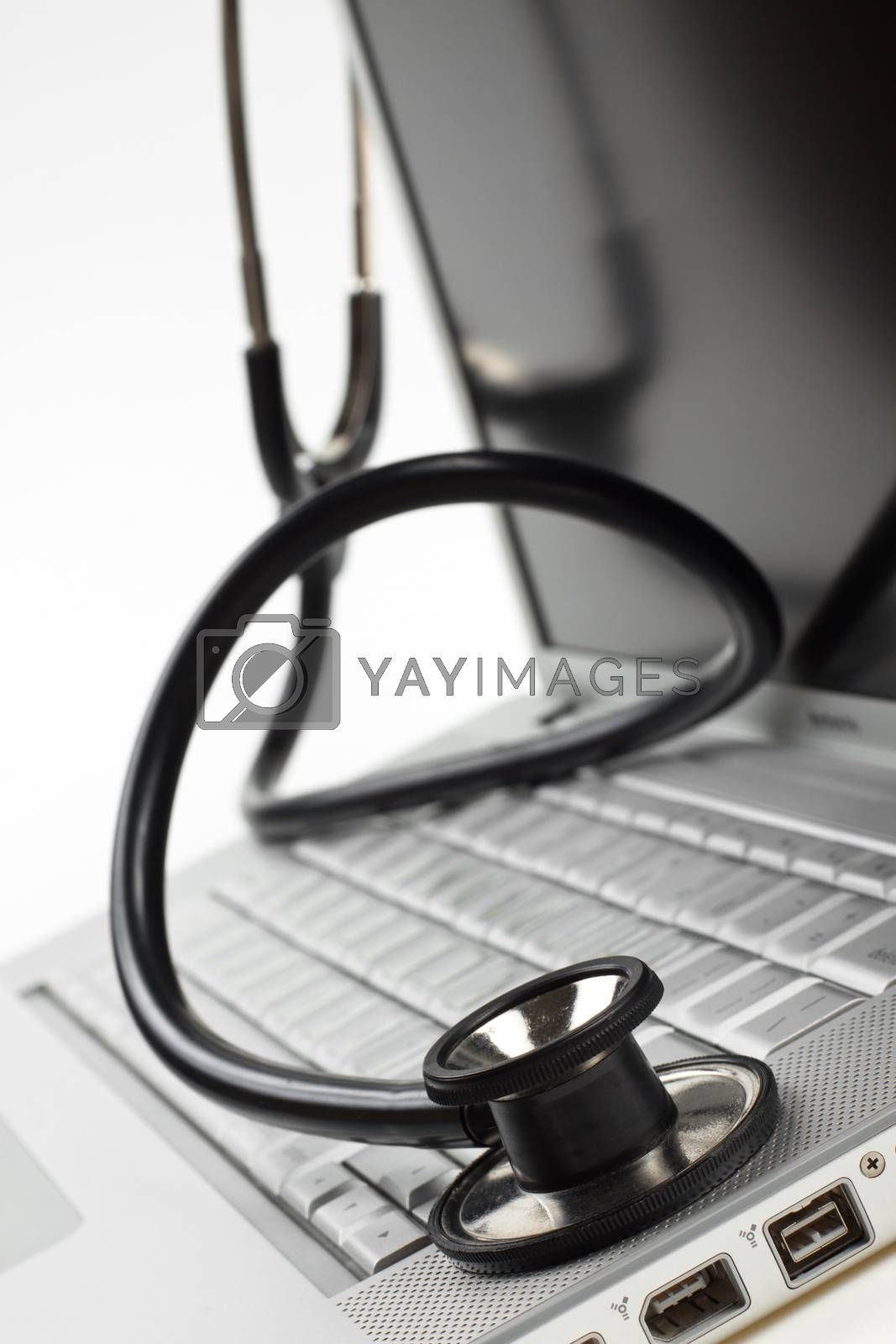 silver laptop diagnosis with black stethoscope crop closeup isolated on white background