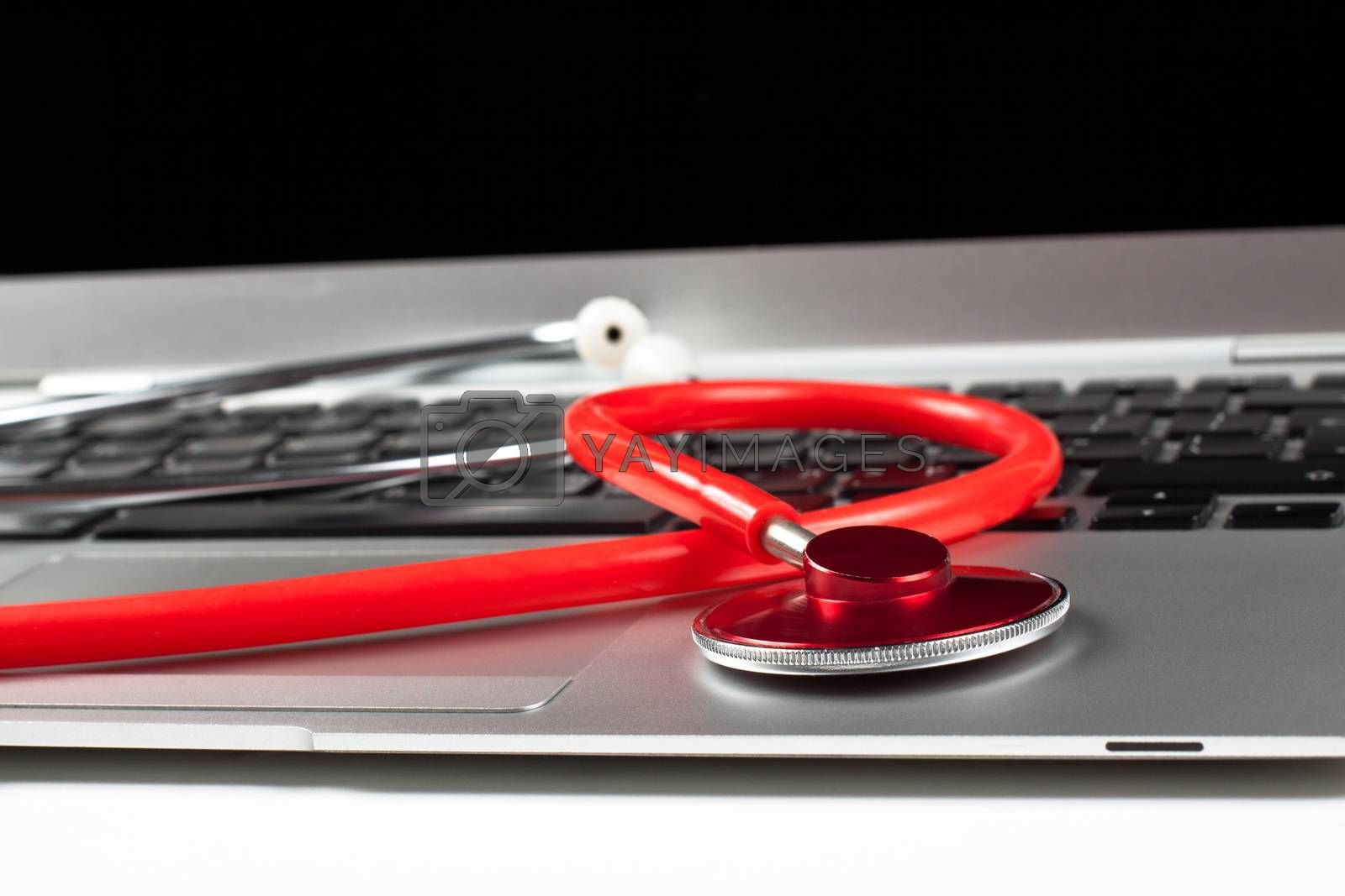 silver laptop diagnosis with black screen and red stethoscope closeup focus on the stethoscope