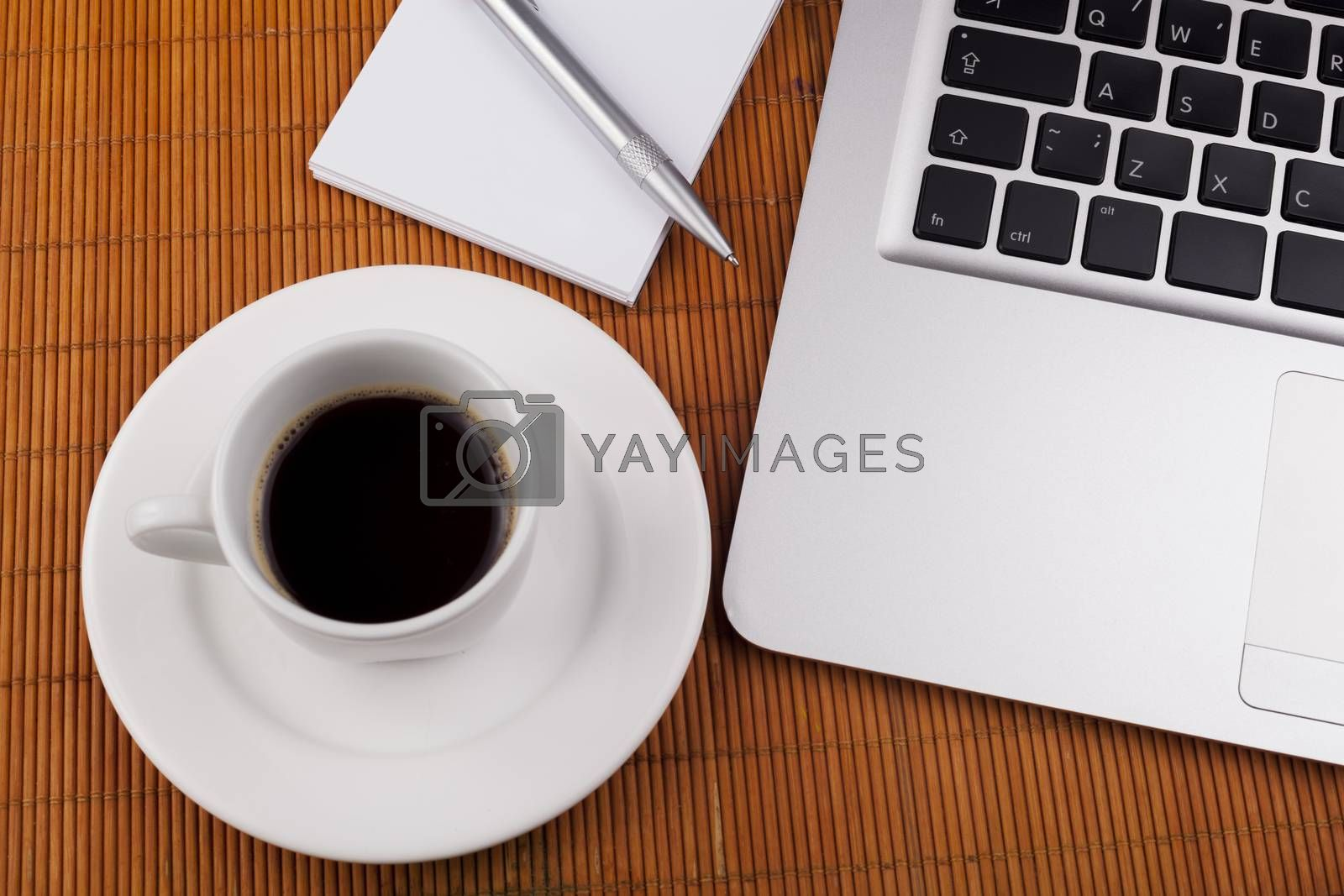 Morning coffee close-up witn laptop pen and white notebook on brown background