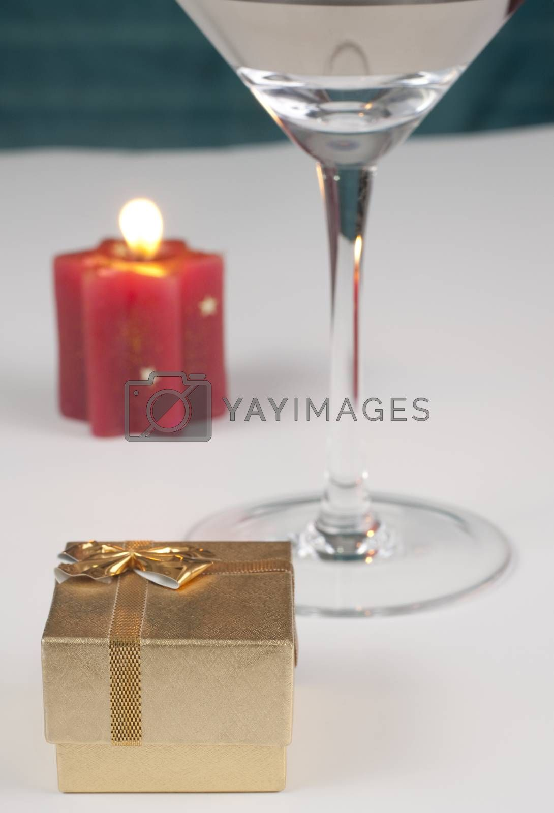 romantic proposal theme with a golden ring box a shampain glass and a red candle with flame