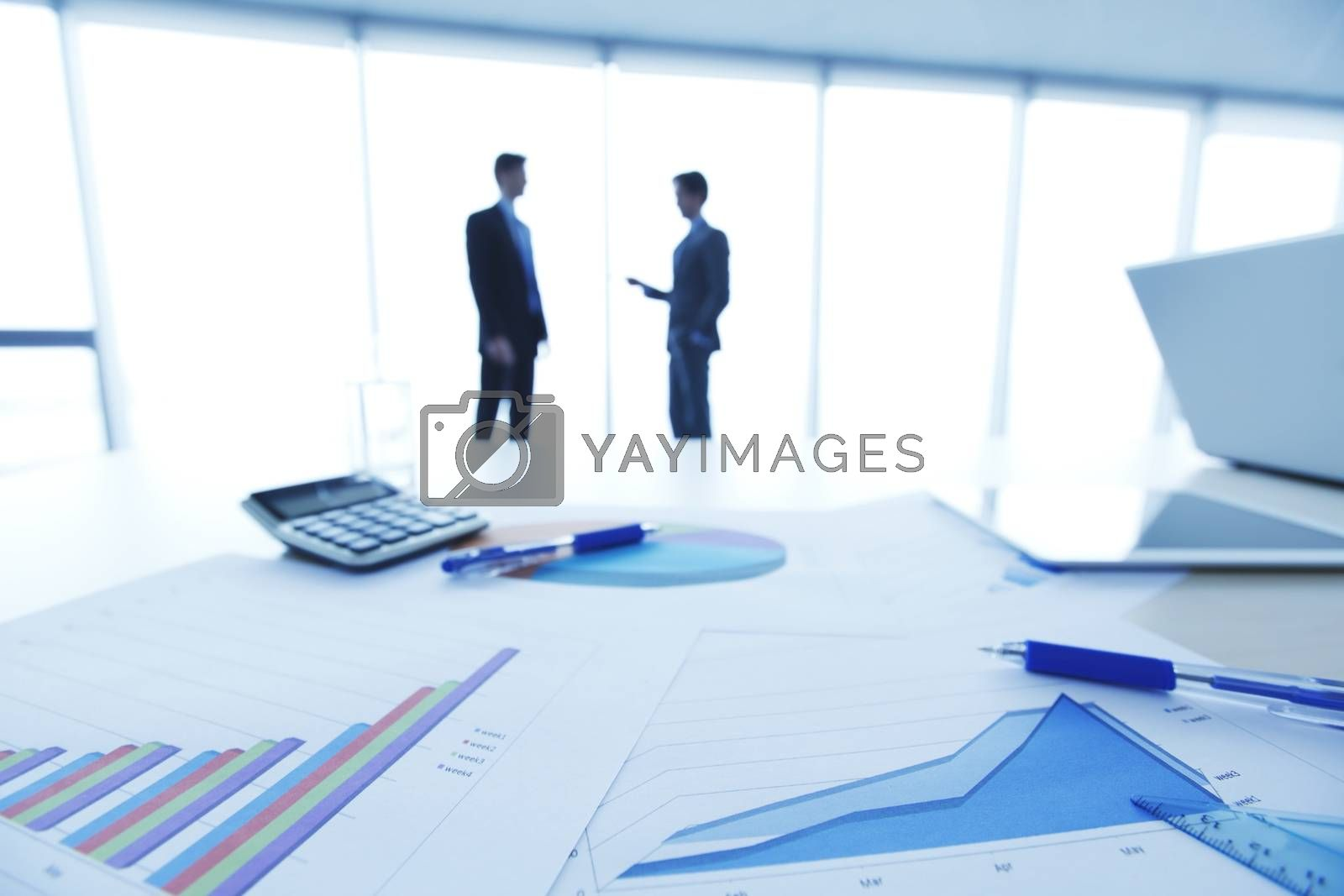 Financial documents , laptop, calculator on table , business team on background