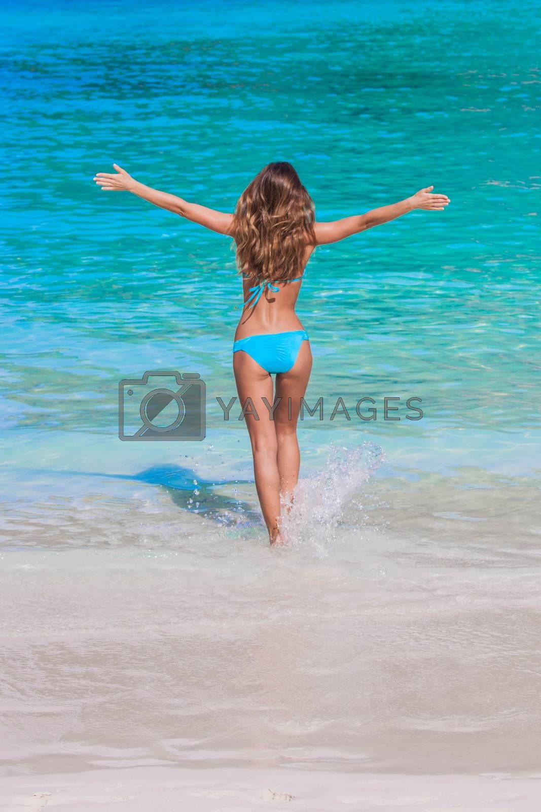 Beautiful happy girl walking to tropical sea with arms raised