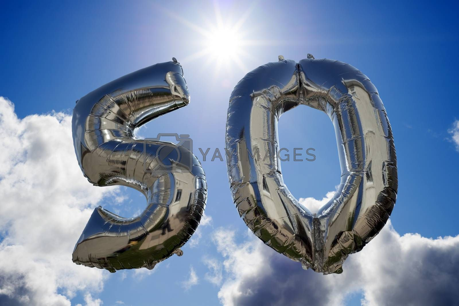 silver balloons for a 50th anniversary floating among the clouds