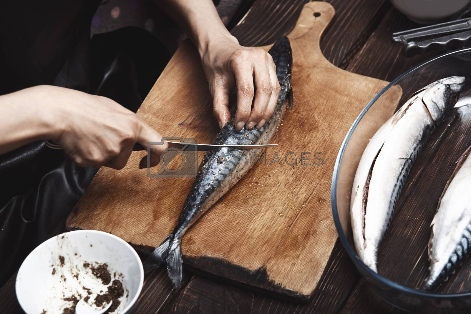 Woman preparing mackerel fish by Novic