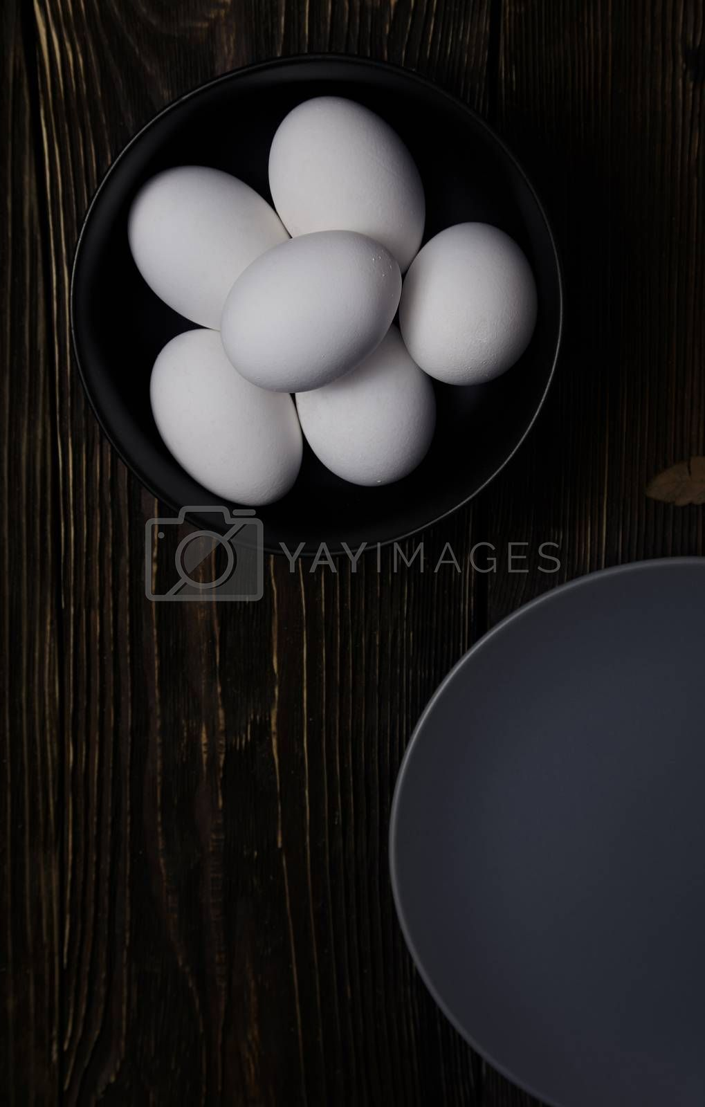 Chicken eggs in plate on a wooden table