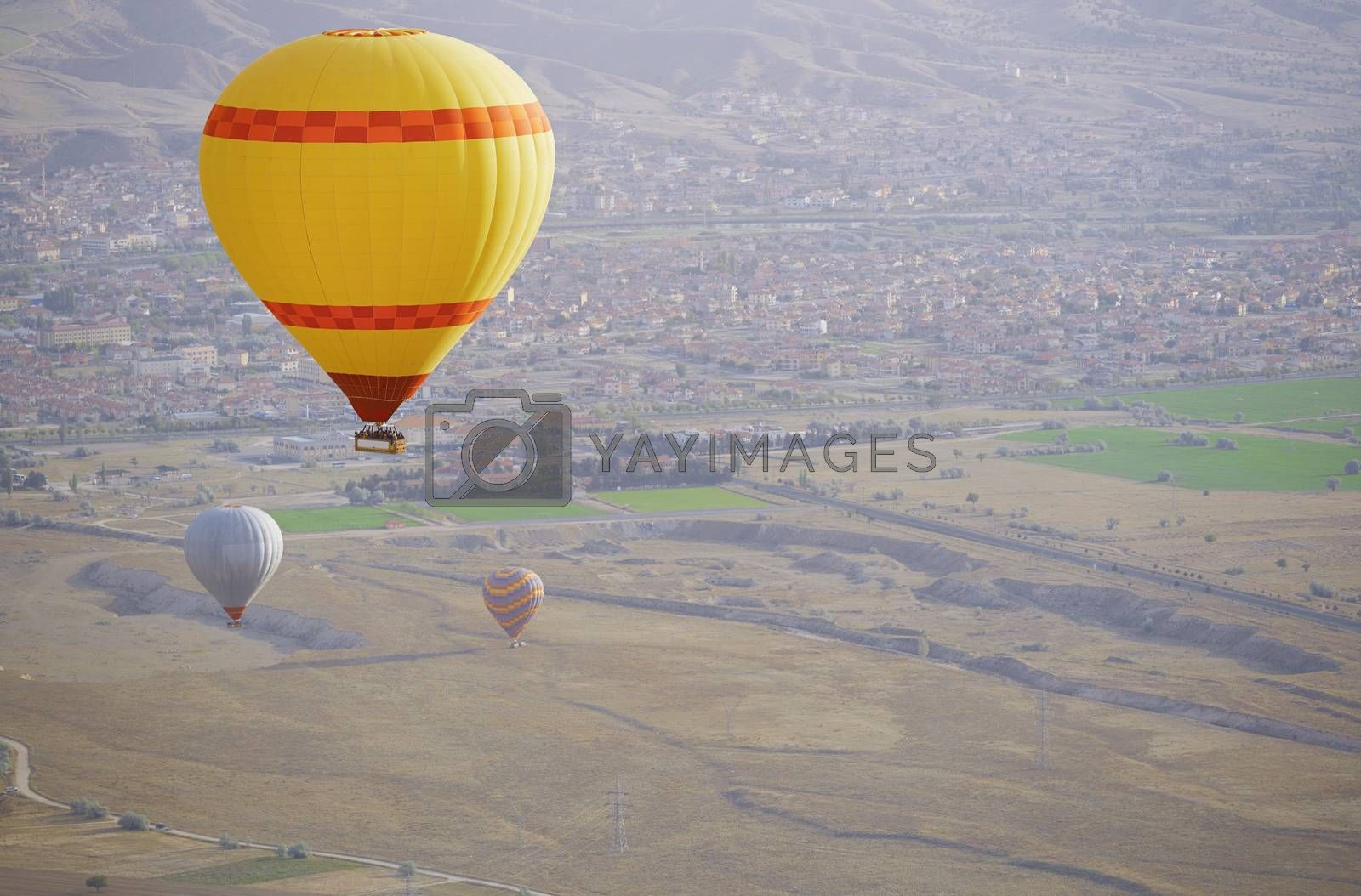 Three air balloons flying over the land. Front view