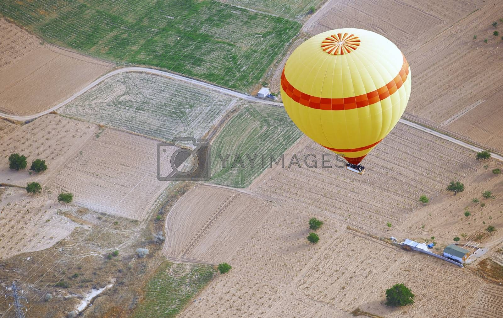 Yellow hot air balloon flying over the land