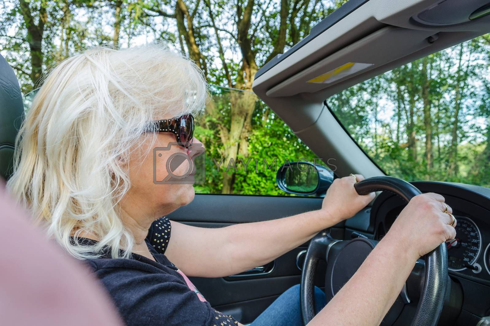 Happy woman driving a convertible in a classic sports car