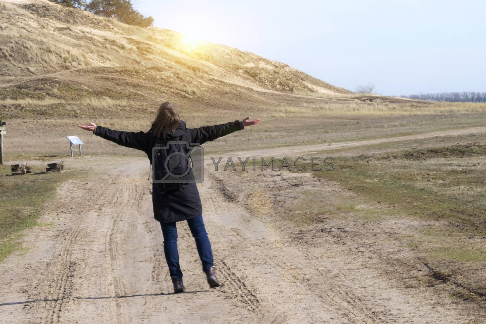 Caucasian woman in black coat arms raised on empty road towards sunset