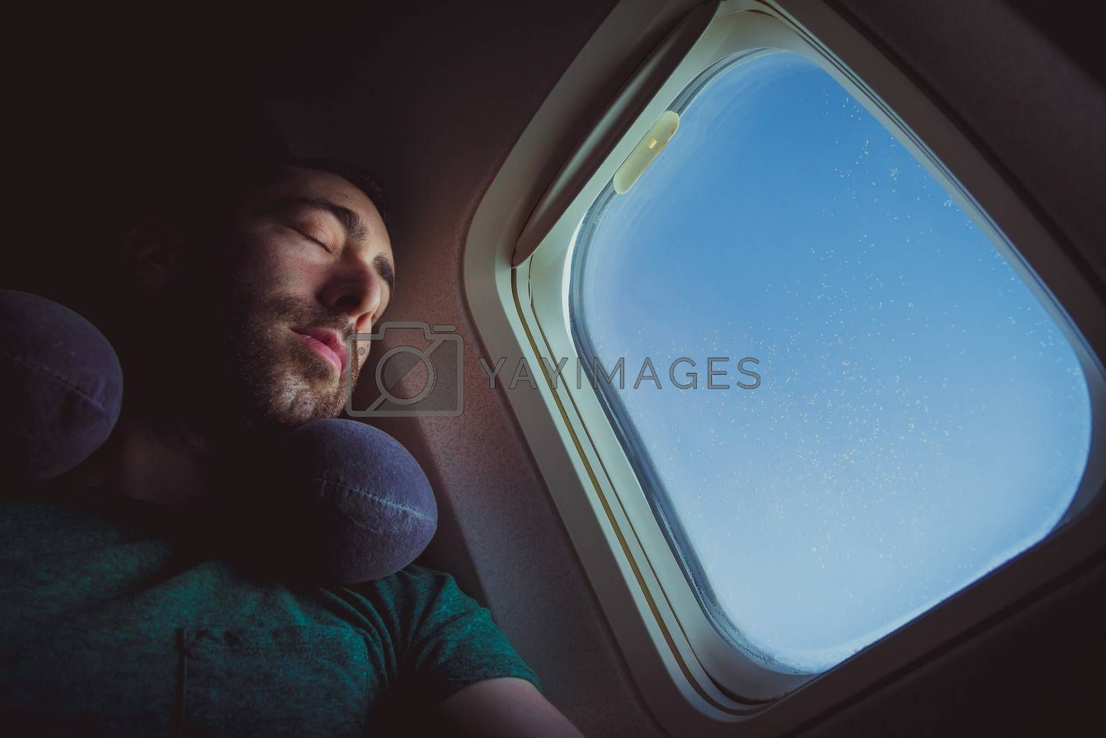 Young man with neck pillow resting and sleeping on an airplane.