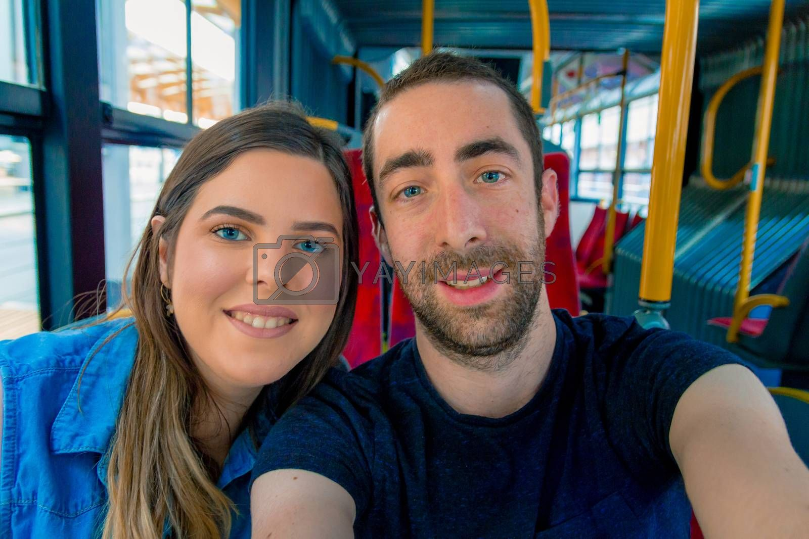 Happy couple taking a selfie with smartphone or camera inside a city bus.