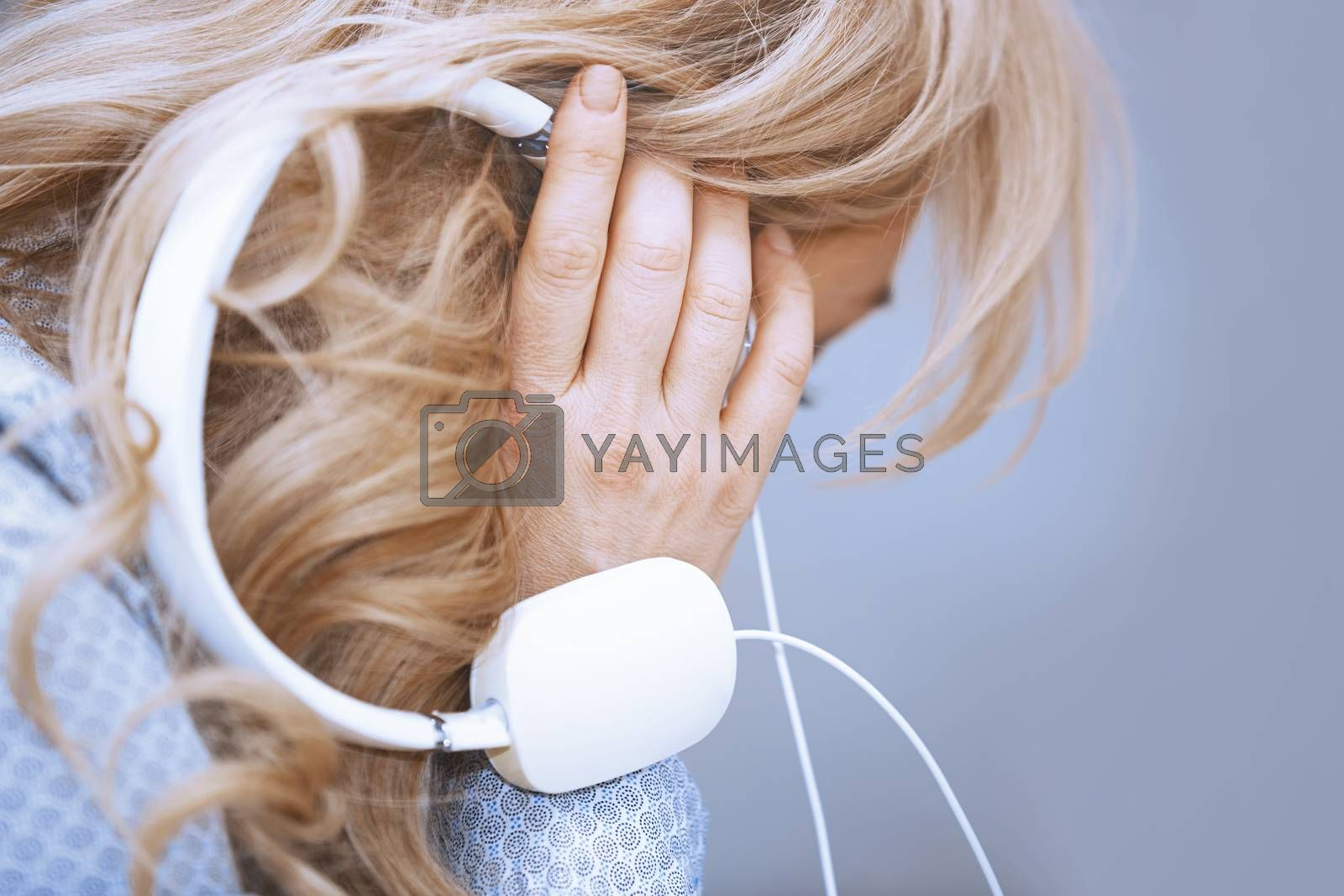 Royalty free image of Blond woman listening music via headphones by Novic