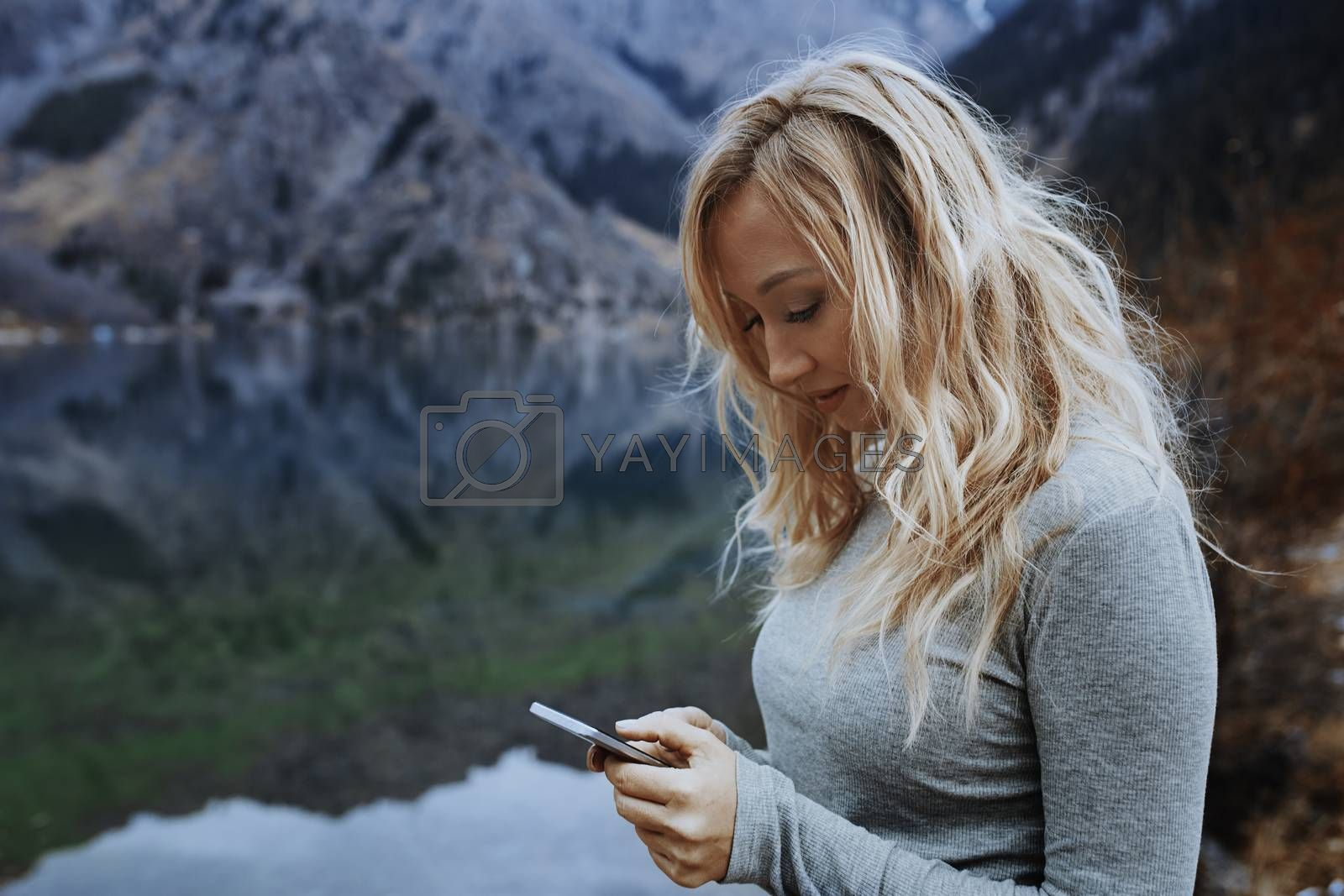 Woman using smartphone at the lake