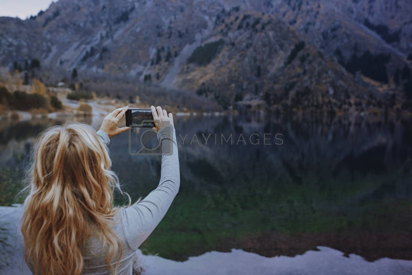 Woman making mobile photo at the mountain lake