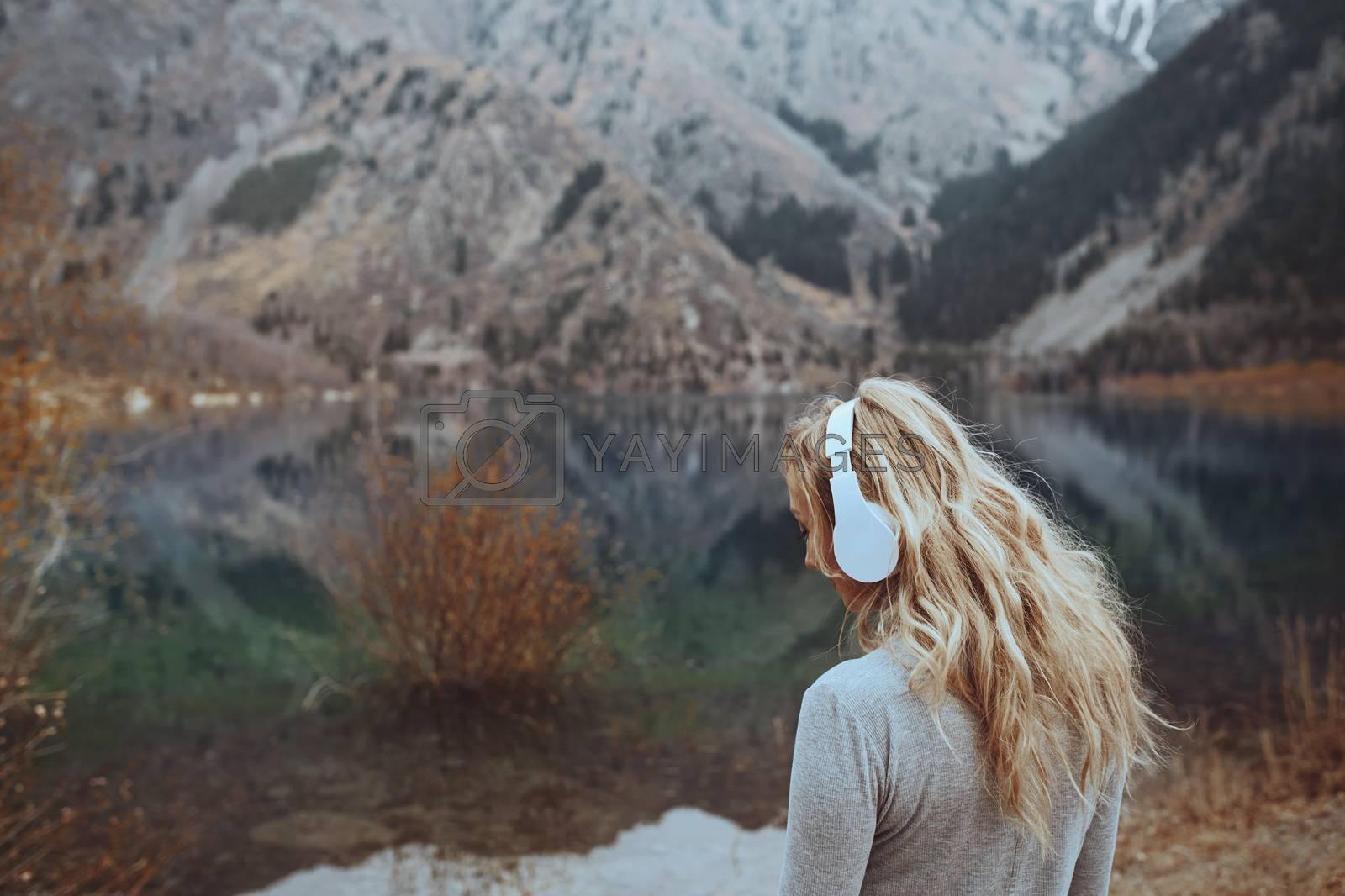 Woman wearing wireless headshot at the mountain lake