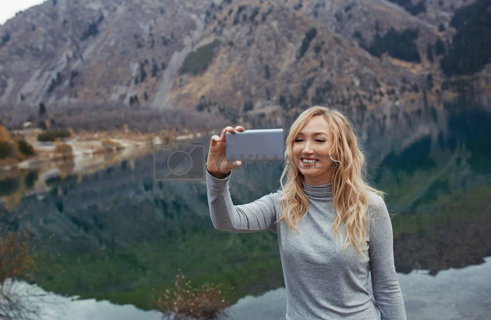 Smiling woman makes selfie at the mountain lake