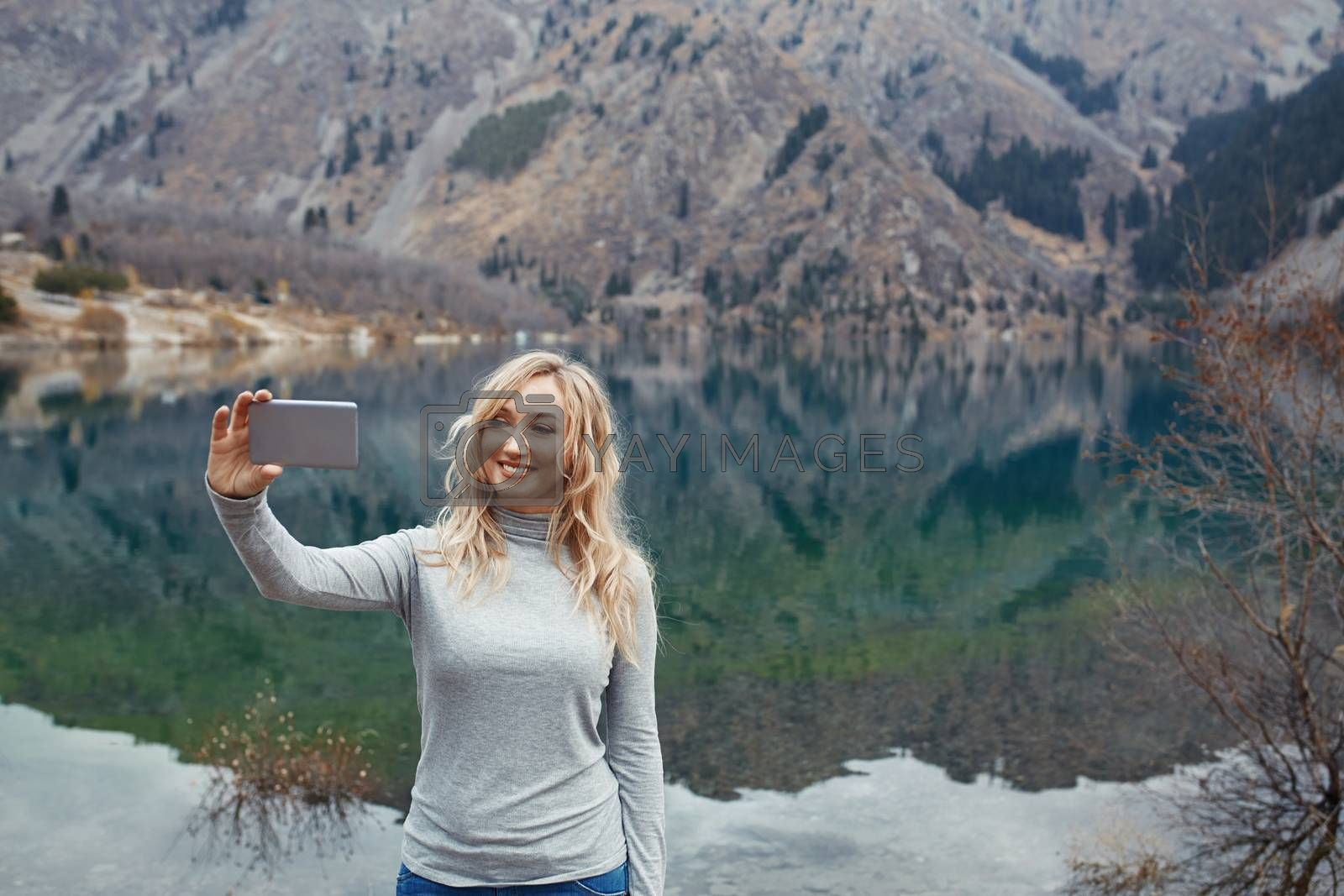 Royalty free image of Smiling woman makes selfie at the mountain lake by Novic