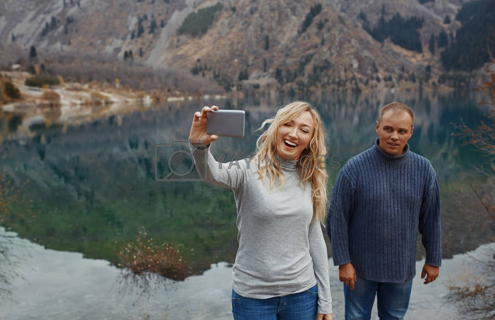 Couple making selfie at the mountain lake