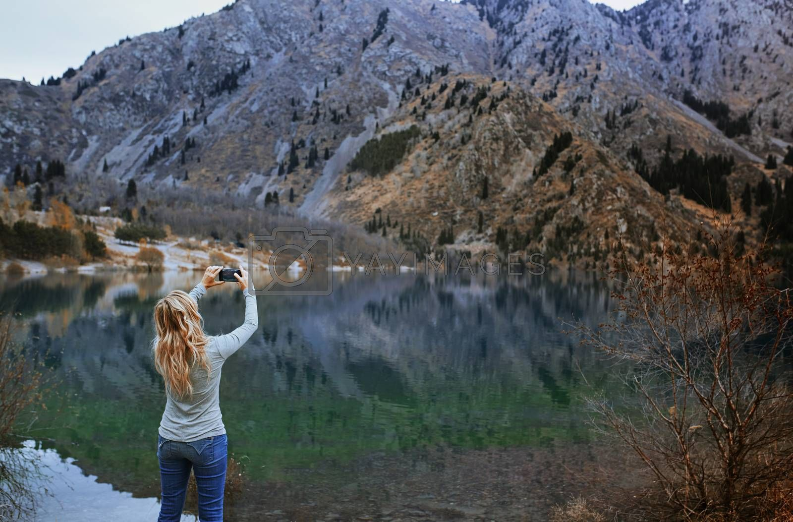 Royalty free image of Woman making mobile photo at the mountain lake by Novic