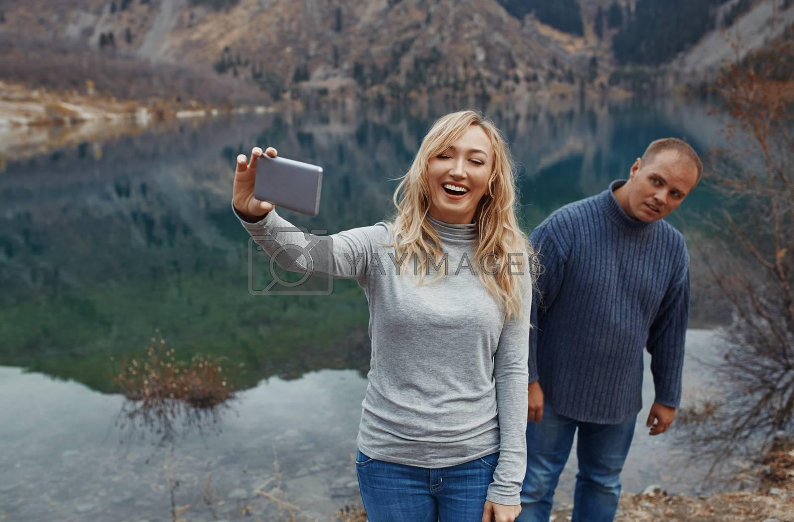 Couple making selfie at the mountain lake