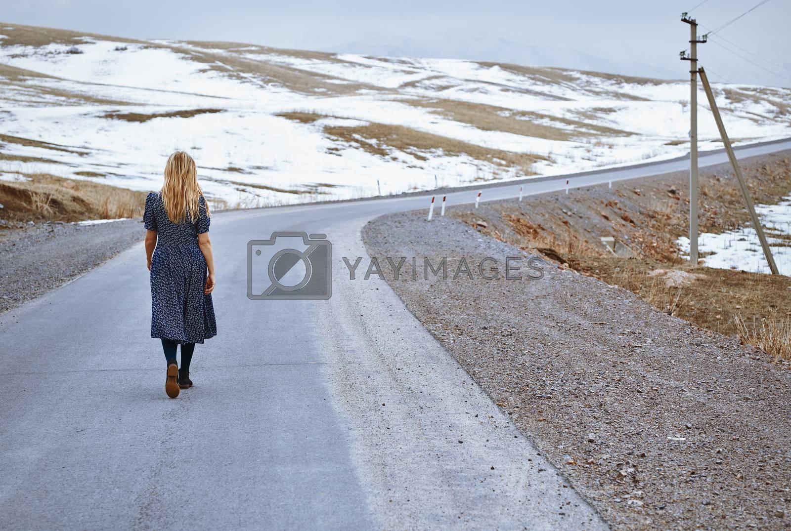 Woman walking along the rural highway