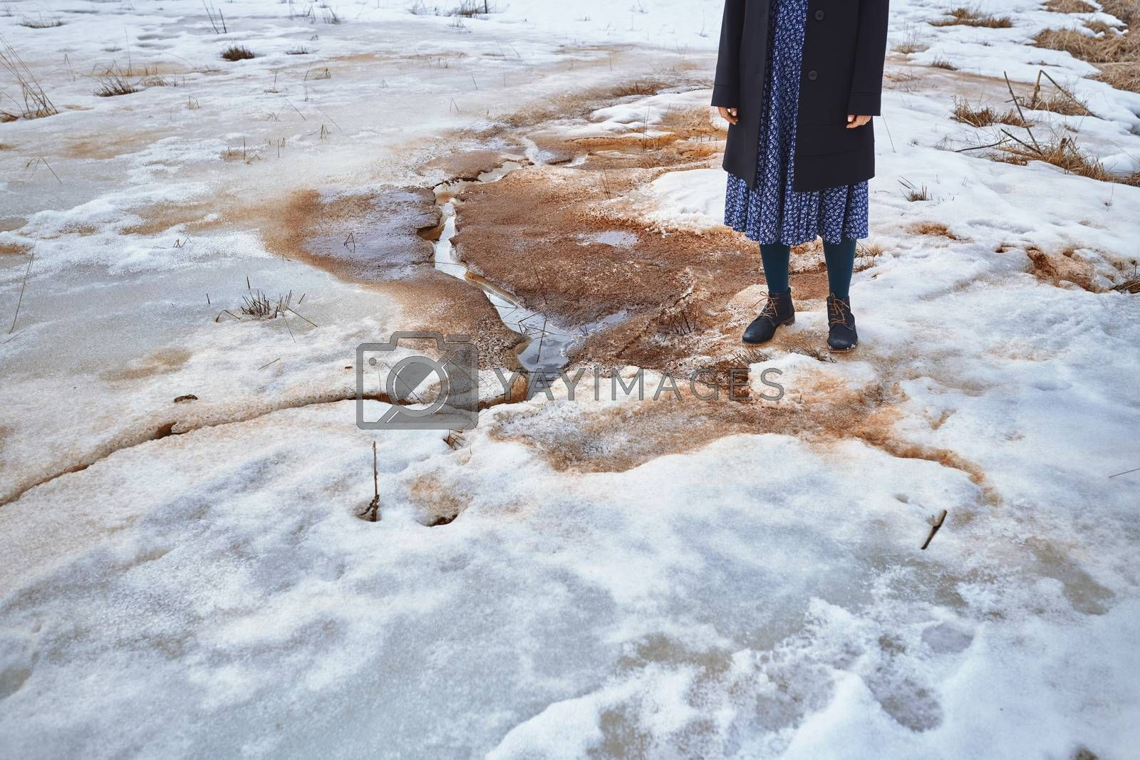Woman standing at the puddle in winter landscape
