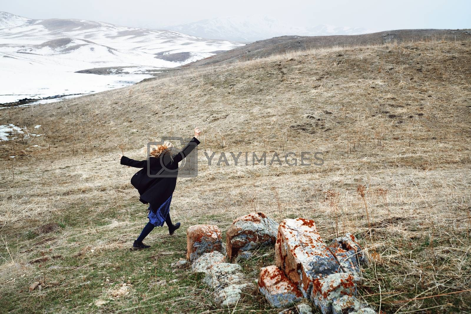 Woman running away in the snow landscape