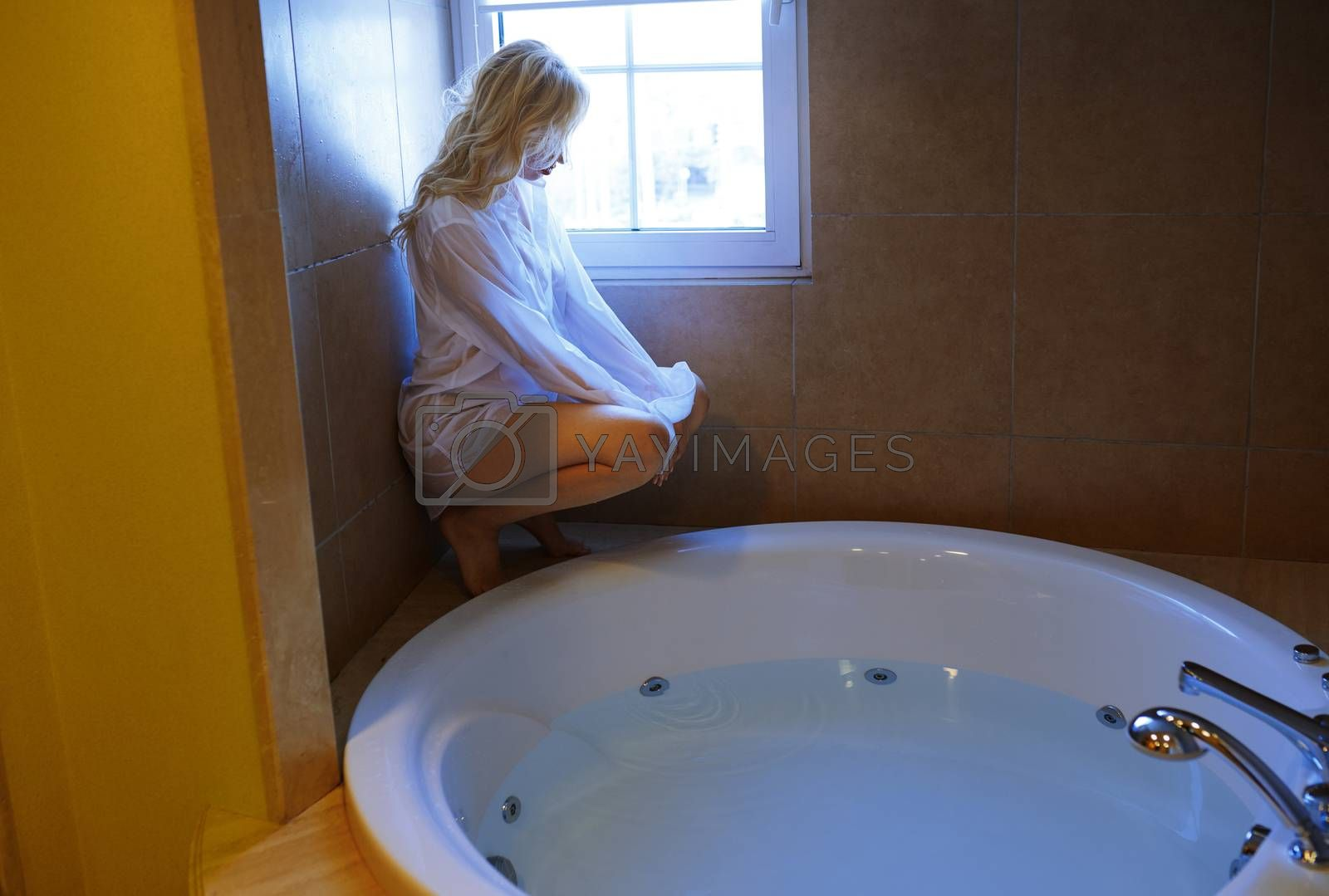Blond woman squatting at the bath